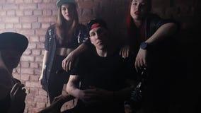 O grupo de meninas atrativas cerca o homem do hip-hop na frente da parede de tijolo, sala escura filme
