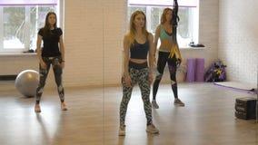 O grupo de meninas bonitas faz a ginástica aeróbica Aptidão A menina atrativa treina ativamente seu corpo filme