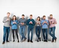 O grupo de meninos e de meninas conectou com seus smartphones Conceito do Internet e da rede social imagem de stock