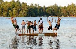 O grupo de miúdos salta no lago Imagens de Stock Royalty Free