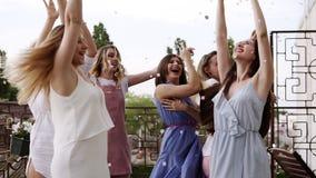 O grupo de moças vestiu-se em partying ocasional fora em confetes da prata do terraço no ar no dia durante o seu video estoque