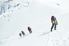 O grupo de montanhistas alcança a parte superior do pico de montanha Escalada e imagem de stock