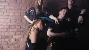 O grupo de mulheres atrativas cerca o homem do hip-hop na frente da parede de tijolo, sala escura filme