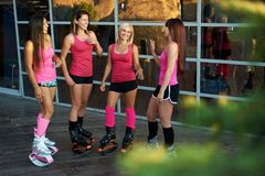 O grupo de mulheres da aptidão vestidas no sportswear fala antes que exercício de salto do kangoo fotos de stock royalty free