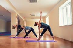 O grupo de mulheres magros novas estica na classe da ioga fotografia de stock