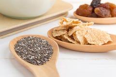 O grupo de passas, grão inteira do trigo lasca-se e sementes do chia no woode imagem de stock royalty free