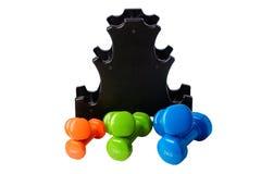 O grupo de pesos isolados coloridos para o esporte em um fundo branco dobrou-se próximo a um suporte preto especial Imagens de Stock