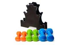 O grupo de pesos isolados coloridos para o esporte em um fundo branco dobrou-se próximo a um suporte preto especial Imagem de Stock Royalty Free