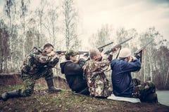 O grupo de pessoas com armas apontou ao céu e preparou-se para fazer um tiro imagem de stock
