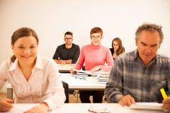 O grupo de pessoas de idade diferente que senta-se na sala de aula e atende Imagens de Stock Royalty Free