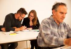 O grupo de pessoas de idade diferente que senta-se na sala de aula e atende Foto de Stock