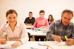 O grupo de pessoas de idade diferente que senta-se na sala de aula e atende Imagens de Stock