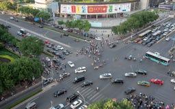 O grupo de pessoas que cruza uma avenida alta do tráfego na cidade de seja fotografia de stock royalty free