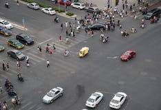 O grupo de pessoas que cruza uma avenida alta do tráfego na cidade de seja foto de stock