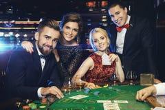 O grupo de povos ricos está jogando o pôquer no casino fotografia de stock