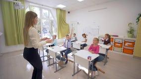 O grupo de principiantes levanta as mãos para responder na lição ao sentar-se na mesa na frente do professor ao quadro-negro na e vídeos de arquivo