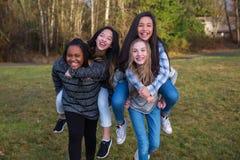 O grupo de quatro crianças que jogam e que dão às cavalitas monta imagens de stock royalty free