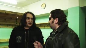 O grupo de rock Kukryniksy Alex Gorshenev do membro dá a entrevista ao homem brutal no casaco de cabedal dos óculos de sol video estoque