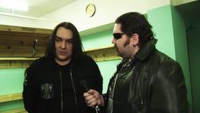 O grupo de rock Kukryniksy Alex Gorshenev do solista dá a entrevista em de bastidores ao homem no casaco de cabedal filme