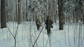 O grupo de soldados corre em esquis nas madeiras com armas grampo Soldados com corrida dos rifles e dos lançadores de granadas de vídeos de arquivo