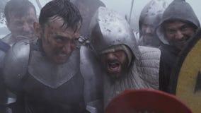 O grupo de soldados feridos na armadura de placa está recolhendo após a batalha filme