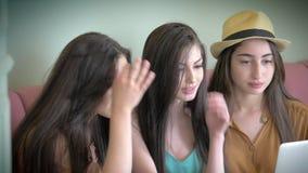 O grupo de três amigas bonitas olha a conversa que da tela do portátil os trabalhos em rede sociais com amigos têm o divertimento video estoque