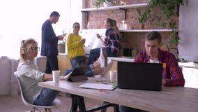 O grupo de trabalhadores de escritório novos bem sucedidos é comendo e de trabalho com tabuletas e portáteis na cozinha durante a