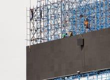 O grupo de trabalhadores está escalando polos para instalar quadros de avisos do diodo emissor de luz Foto de Stock Royalty Free
