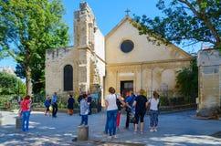 O grupo de turistas desconhecidos é na frente da igreja velha do Saint-Julien-le-Pauvre no quarto latino, Paris, França imagens de stock royalty free