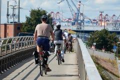 O grupo de turistas em bicicletas vai ao porto de Hamurgh imagem de stock royalty free