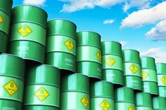 O grupo de verde empilhou cilindros do combustível biológico contra o céu azul com nuvem Fotografia de Stock