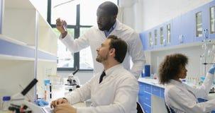 O grupo diverso de cientistas que trabalham no laboratório moderno, dois colegas masculinos discute exemplos em uns tubos de ensa filme