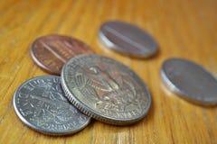 O grupo do dólar de um quarto de prata inventa a moeda nos EUA, dólar americano no fundo de madeira Foto de Stock