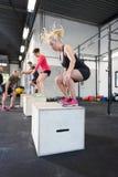 O grupo do exercício treina saltos da caixa no gym da aptidão imagem de stock royalty free