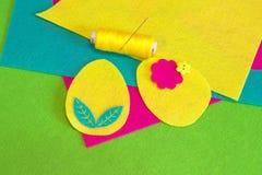 O grupo do ornamento do ovo da páscoa, linha, agulha, botão da flor, feltro colorido cobre em um fundo verde Como costurar o ovo  imagens de stock royalty free