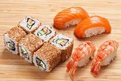 O grupo do sushi com rolos e o nigiri serviram em uma placa de madeira Imagens de Stock Royalty Free