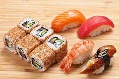 O grupo do sushi com rolos e o nigiri serviram em uma placa de madeira Fotos de Stock Royalty Free