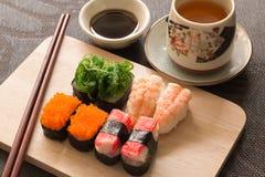 O grupo do sushi com varas da costeleta e molho de soja serviu na ardósia de madeira Imagens de Stock Royalty Free