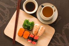 O grupo do sushi com varas da costeleta e molho de soja serviu na ardósia de madeira Fotos de Stock Royalty Free