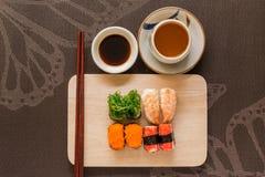 O grupo do sushi com varas da costeleta e molho de soja serviu na ardósia de madeira Imagem de Stock
