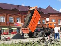 O grupo do trabalho coloca o asfalto na estrada imagens de stock