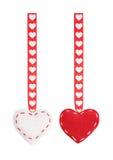 O grupo dos corações de matéria têxtil do vermelho dois que penduram em uma fita com um teste padrão dos corações Foto de Stock