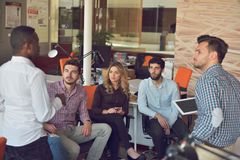 O grupo dos jovens no escritório moderno tem a reunião e a sessão de reflexão da equipe ao trabalhar no portátil e no café bebend imagens de stock