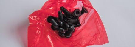 O grupo dos parafusos no saco de plástico vermelho imagem de stock royalty free