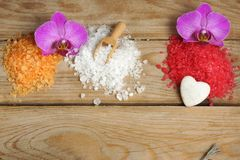 O grupo dos termas com corrediças multi-coloridas do sal e da orquídea de banho do mar floresce em um fundo de madeira Fotografia de Stock Royalty Free