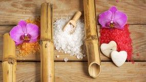 O grupo dos termas com corrediças multi-coloridas dos tubos de sal de banho do mar, de bambu e da orquídea floresce em um fundo d Imagem de Stock Royalty Free