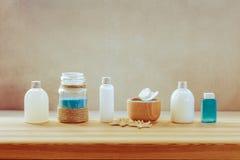 O grupo dos termas de garrafas com gel do banho, o champô, o leite do corpo e o azul esfregam com sal do mar foto de stock royalty free