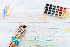 O grupo e a caixa de escovas da pintura com as aquarelas na tabela manchada de madeira branca com espirram, fundo artístico para  fotos de stock