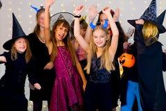 O grupo feliz de adolescentes dança em trajes de Dia das Bruxas fotografia de stock