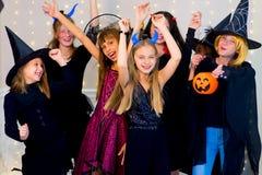 O grupo feliz de adolescentes dança em trajes de Dia das Bruxas imagem de stock royalty free